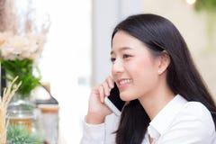 Talande telefon för härlig ung asiatisk kvinna och leende i coffee shop, affärskvinnasammanträde i fri tid för kafé Fotografering för Bildbyråer