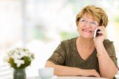Talande telefon för hög kvinna Arkivfoto