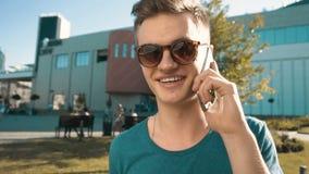 Talande telefon för ung man stock video