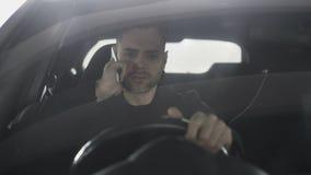 Talande telefon för uppriven och ilsken man, medan sitta inom bilen utomhus arkivfilmer