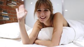Talande ung kvinna som ligger i säng, online-video pratstund, Webcamsikt Arkivbild