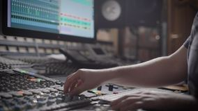 Talanted dj is creating music in a recording studio on a mixing console.