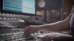 Talanted DJ sta creando la musica in uno studio di registrazione su una console di miscelazione video d archivio