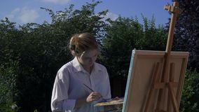 Talanted girl artist. Draws paints on an easel in the courtyard stock footage