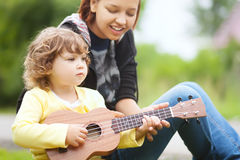 Talanted toddler girl learn to play ukulele guitar. Young attractive nanny teachs little girl playing ukulele, sunny day, outdoors. Early music education Stock Photo