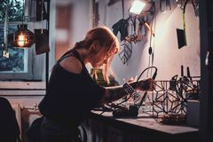 Diligent woman is working on her own project at glass workshop. stock images