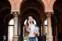Talar hållande anteckningsböcker för ursnygg lycklig student telefonen på universitetsområde på högskolan Royaltyfri Foto