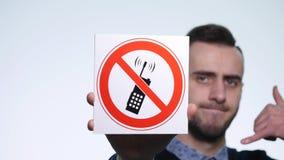Talar hållande tecken` för den unga mannen inte på telefon`en på en vit bakgrund stock video
