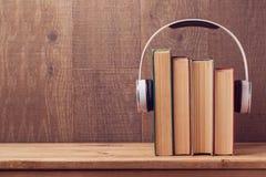 Talbokbegrepp med gamla böcker och hörlurar över träbakgrund Arkivfoton