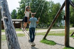 TALCZY,IRKUTSKAYA OBLAST,俄罗斯- 2017年8月7日在木摇摆的,夫妇在树附近和老木房子获得乐趣 免版税库存图片