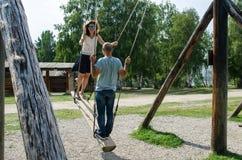 TALCZY, IRKUTSKAYA OBLAST, RUSSIA - 7 AGOSTO 2017, si accoppiano su un'oscillazione di legno vicino all'albero e la vecchia casa  immagine stock libera da diritti