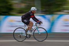 TALDYKORGAN KASAKHSTAN - MAJ 21, 2017: En äldre manlig idrottsman nen rider en vägcykel arkivfoton