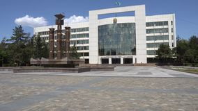 Taldykorgan Regional Akimat. Taldykorgan Akimat City Hall of Almaty region frontal view with waving Kazakh flag and fountain at background on a sunny blue sky stock video