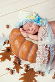 Tale of Cinderella. Little beautiful newborn baby girl in a bonnet sleeping on a pumpkin Stock Photo