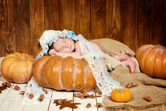 Tale of Cinderella. Little beautiful newborn baby girl in a bonnet sleeping on a pumpkin Royalty Free Stock Photography