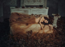 Tale of Sleeping Beauty. The girl is in the old, abandoned room. It covered the dust and leaves. Autumn atmosphere of sadness. Beautiful, long, wavy hair stock photos