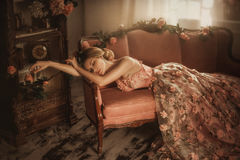 Tale of Sleeping Beauty. The girl is in the old, abandoned room. It covered the dust and roses. Summer atmosphere of sadness. Creative colors stock photo