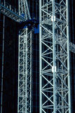 Tale of two towers. Two side by side construction crane towers. White towers against a dark blue backdrop of steel and glass. This vertical shot is timeless and Royalty Free Stock Image
