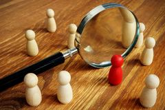 Talent acquisition and management. Magnifying glass and figurines. Talent acquisition and management. Magnifying glass and wooden figurines stock images