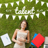 Talent against pretty student lying on grass Stock Photography