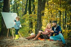Talent development. Painting skills. Mom and dad relax park picnic while kid painting. Rest and hobby concept. Parents. Relaxing while their son painting stock image