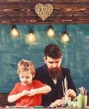 Talent en creativiteitconcept Kind en leraar die op bezige gezichten, het trekken schilderen Leraar met baard, vader en weinig royalty-vrije stock afbeelding