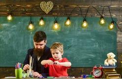 Talent en creativiteitconcept Leraar met baard, vader en weinig zoon in klaslokaal terwijl het trekken, het creëren stock foto