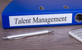 Talent management folder. Blue folder with white label reading talent management on desktop with pen and calculator stock photos