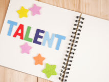 Talent management. Word spell Talent and star on blank notebook with wood background (Business Concept stock images