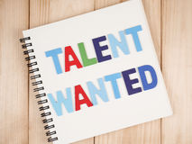 Talent management. Word spell Talent Wanted on blank notebook with wood background (Business Concept royalty free stock photography