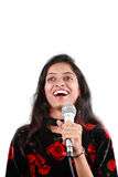 Talent Show Host. A beautiful talent show host talking to the audience holding a mic, on white studio background Royalty Free Stock Photos
