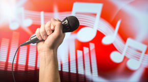 Talent show and singing live. Singing, karaoke or vocal training concept. Microphone in hand in front of an abstract music themed note and equalizer background Royalty Free Stock Images