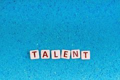 Talent word on stone. Talent word write in square white stone on blue sand, free space for your text royalty free stock image