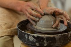 Talented accurate man being professional pottery master. Producing on wheel. Talented accurate man being professional pottery master and molding fresh pot stock image
