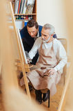 Talented artist helping elderly man in painting Royalty Free Stock Image