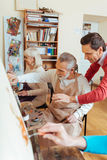 Talented artist helping elderly man in painting studio Royalty Free Stock Photography