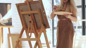 Talented artist inspired paints picture on canvas mounted on easel. In hands holds brush and palette, in background large light window and other works of stock video