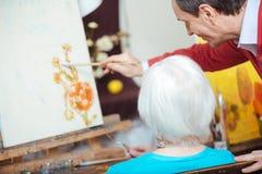 Talented artist teaching elderly woman in painting school Royalty Free Stock Photo