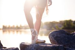 Talented ballerina with pointe shoes on the beach at sunset stock photography