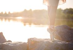 Talented ballerina with pointe shoes on the beach at sunset royalty free stock photos
