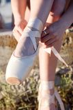 Talented ballerina with pointe shoes on the beach at sunset royalty free stock image