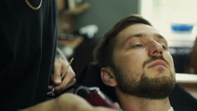 Talented bearded barber is trimming the beard of his client in a black cutting hair cape in the barbershop. He is using stock footage