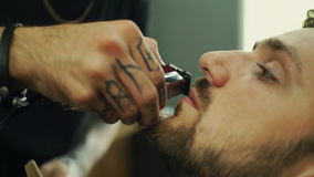 Talented bearded barber is trimming the beard of his client in a black cutting hair cape in the barbershop. He is using. A cutting comb and a hair clipper stock footage