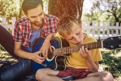 Talented boy is looking on strings and playing guitar. His father is sitting besides him and helping him. Adult is. Smiling Stock Images
