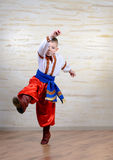 Talented child performing a traditional dance. Talented child wearing Eastern European folk costume with embroidered white shirt and belt, red pants and boots Stock Photos