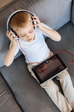 Talented creative kid enjoying music. Little Mozart. Relaxed bright intelligent boy wearing headphones while using his tablet for listening to some cool songs Stock Photo