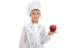 Talented cute boy in white chef uniform holding red apple on white background Stock Photography