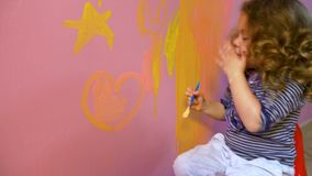 Little girl draws on wall stars and heart stock video footage