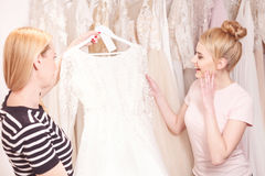 Talented designer showing bridal gown to customer Stock Image