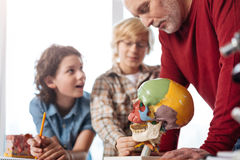 Talented engaging biology teacher explaining skull structure Royalty Free Stock Images